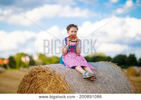 Cute little kid girl in traditional Bavarian costume in wheat field. German child with hay bale during Oktoberfest in Munich. Preschool girl eating pretzel during harvest time in Germany