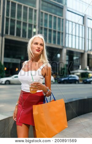 Photo of blonde with drink in hands , packages at city buildings during day