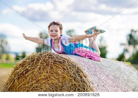 Cute little kid girl in traditional Bavarian costume in wheat field. German child with hay bale during Oktoberfest in Munich. Preschool girl play at hay bales during summer harvest time in Germany