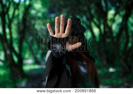 Witch with outstretched hand in black cloak at dark forest