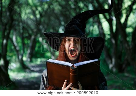 Portrait of young screaming witch with magic book in mystical forest