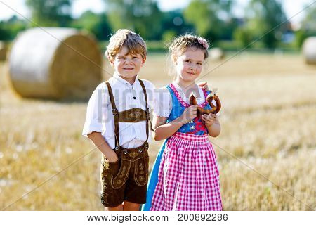 Two kids in traditional Bavarian costumes in wheat field. German children eating bread and pretzel during Oktoberfest. Boy and girl play at hay bales during summer harvest time in Germany