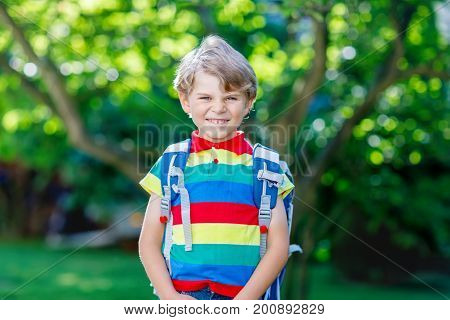 Happy little kid boy in colorful shirt and backpack or satchel on his first day to school or nursery. Child outdoors on warm sunny day, Back to school concept