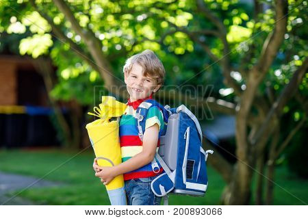 Happy little kid boy in colorful shirt and backpack or satchel and traditional German school bag called Schultuete on his first day to school or nursery. Child outdoors on warm sunny day