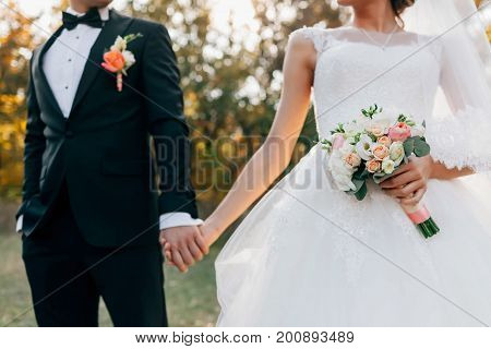 Wedding bouquet. Blurred bride with in a white dress and groom in tuxedo are holding hands. Soft focus on flowers. Outdoors ceremony