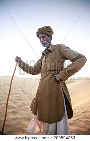 Jaisalmer India - November 24 2009: An old man standing on a dune living in the desert a camel driver
