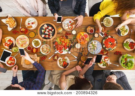 Online at dinner. Gadget device addiction, friends eating with smartphones, browsing in social networks while eating food together, table top view