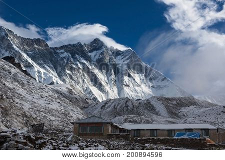 Mountain House In Snow Under Lhotse Mountain Vertical Wall. House In Snowy Mountains On Everest Base