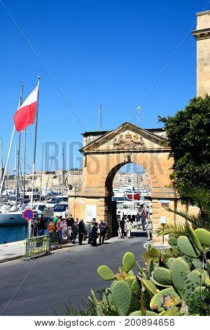 VITTORIOSA, MALTA - MARCH 31, 2017 - Tourists walking through an arch leading to the Grand Harbour marina with prickly pear cactus in the foreground Vittoriosa (Birgu) Malta Europe, March 31, 2017.