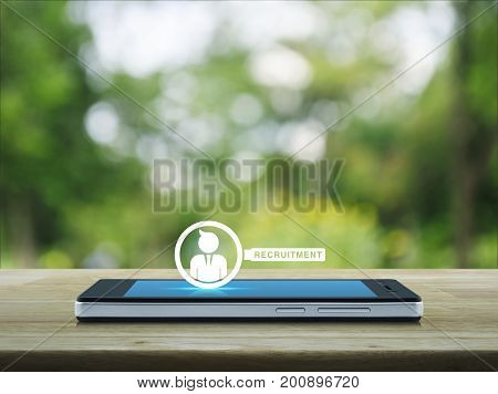Businessman with magnifying glass icon on modern smart phone screen on wooden table over blur green tree in park Recruitment concept