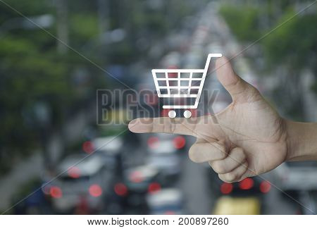 Shopping cart icon on finger over blur of rush hour with cars and road Shop online concept