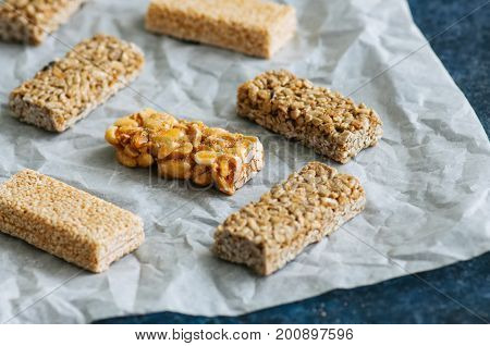 Snacks - mix of energy bars with peanut sesame and sunflower seeds on a blue stone background