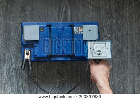 A Man's Hand Holds A Car Battery Tester On A Wooden Background