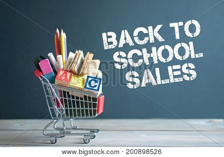 Shopping cart filled with stationery merchandise against chalkboard with sales sign