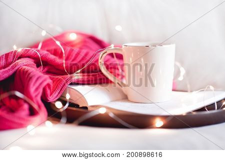 Cup of tea staying on open book with knitted sweater on wooden tray in bed closeup. Good morning. Breakfast.