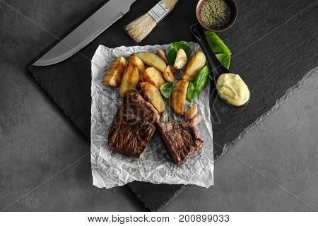 Food paper with delicious steak, garnish and sauce on slate plate