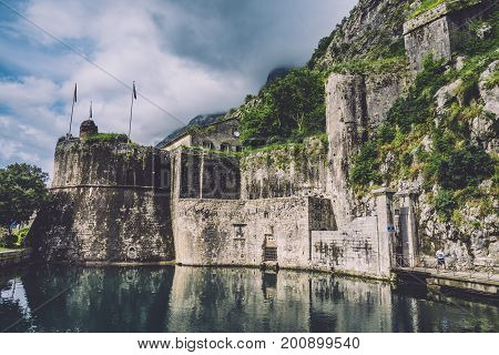 Kotor fortress wall and Old Town Stari Grad with cloudy mountains on the background. Kotor castle San Giovanni reflected on the moat water. Unesco world heritage site in Montenegro.