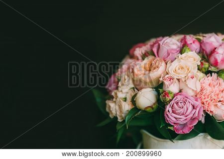 Flower arrangement of white and pink roses at the dark background. Wedding ceremony. Copy space. Close-up