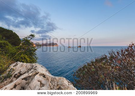 Shoreline and Adriatic sea landscape on the path to Petrovac, Montenegro. Rocks, water and Sveta Nedjelja island by sunset near Perazica Do and Petrovac. Wild Adriatic coast panoramic scene.