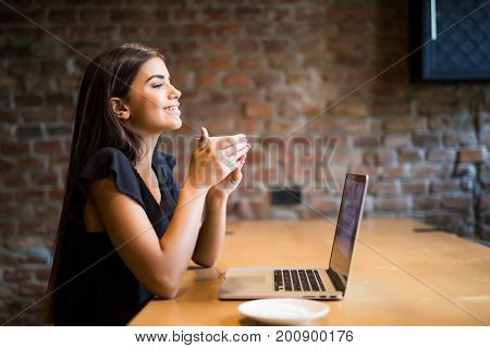 Young Beautiful Woman Drinking Coffee At Cafe Bar In Front Of Laptop.