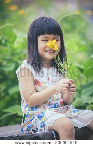 portrait of lovely girl with yellow cosmos flower bouquet in hand toothy smiling face