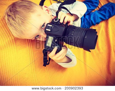 Child passion and hobbies concept. Kid playing with big professional digital camera photographing various things in house