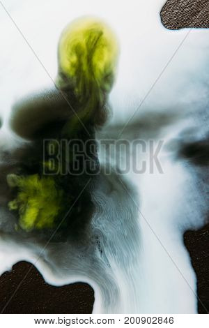 Abstract image of colorful blots of liquid on black background. Watercolor streaks of white paint with green stain on surface flowing each other