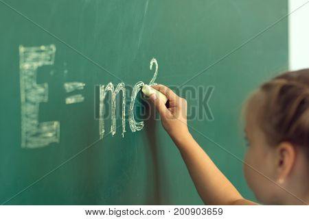 Girl Drawing On Chalkboard Formula E=mc2. Education And School Concept