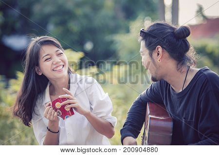 younger asian man and woman relaxing playing guitar in park