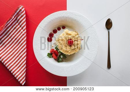 Napoleon cake serving on contrast red and white background. Sweet dessert on plate with decoration from strawberry, cherry and mint, top view with free space