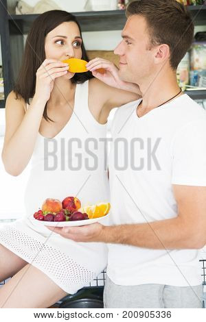 Young man and pregnant woman with fruit plate in the kithen. Pregnancy and nutrition concept