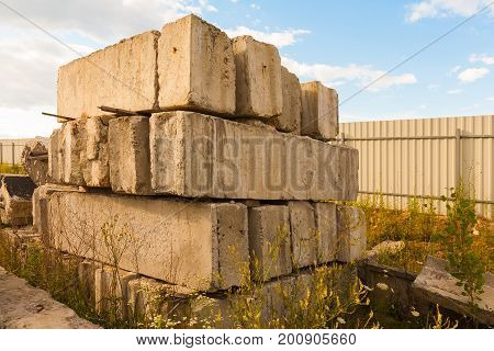 Summer day. On the field near the fence is a construction site. In the frame a group of concrete rectangular blocks stacked in a stack. Horizontal frame