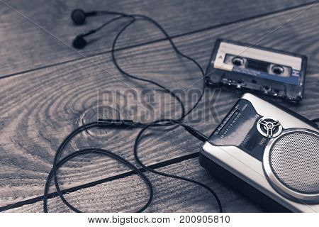 Vintage cassette player with earbuds and tape cassette.Retro style toned image. Selective focus
