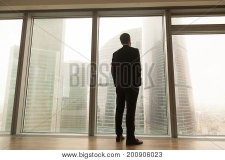 Contemplative businessman standing near big window looking out at city, thoughtful entrepreneur building future plans, thinking over ways to overcome business problems, pass through crisis, back view