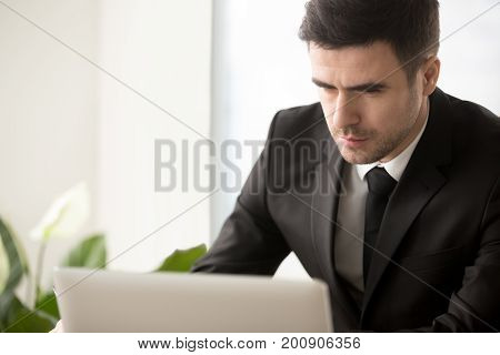 Busy serious businessman focused on working with laptop computer, thinking hard of business task, making decision on online stock exchange, job via internet, using web services, software for business