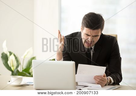 Stressed angry businessman shouting with anger getting bank statement with charges for past due unpaid debt, receiving paper with bad financial results, facing huge bills, big taxes, written warning