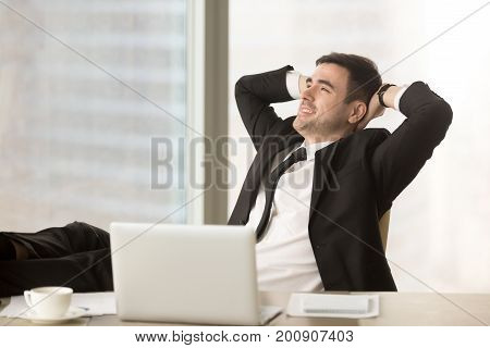 Happy relaxed businessman resting hands behind head near pc laptop looking away sitting at office desk with feet up on table, finished work, job done, completed all tasks, relaxing after hard workday