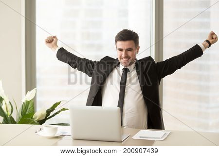 Happy businessman in suit raising hands looking at laptop, celebrating victory, stock trading win, got job interview invitation, motivated with good work result, achieving goal, business success