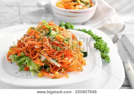 Plate with delicious spicy carrot spaghetti on table