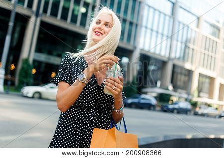 Photo of model with drink, with purchases near buildings in city during day