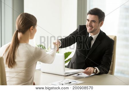 Smiling friendly businessman shaking hands with woman sitting at office desk, holding agreed negotiation document, congratulating female partner with successful deal, handshaking new team member, HR