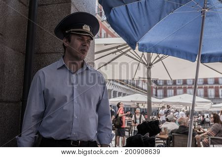 Madrid, Spain - August 6, 2017 - A man wearing a Russian military cap waits in a corner of the Plaza Mayor in Madrid.