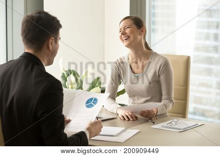Happy colleagues laughing during pleasant funny conversation in office, positive businesspeople having fun at meeting while working, businesswoman screaming with laughter after partner told joke