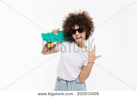 Young crazy woman showing rock gesture while standing and holding skateboard isolated over white background