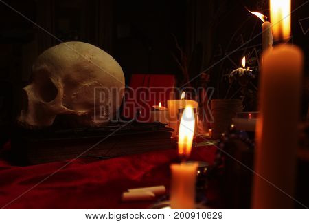 Witchcraft composition with human skull, candles, magic book and pentagram symbol. Halloween and occult concept, black magic ritual.