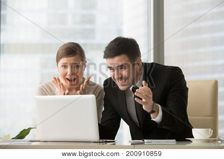 Surprised office people looking at laptop screen with amazement, shocked by good breaking news, fantastic discount, special offer, online business growth, big win or great success, can not believe it