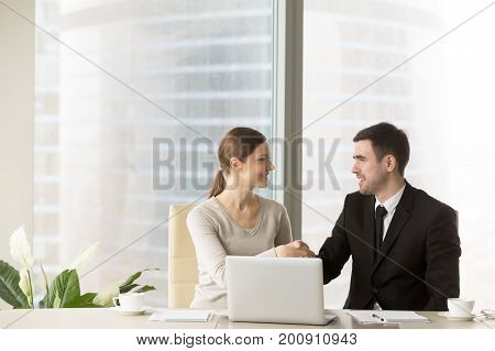 Smiling businessman shaking hands with businesswoman in office, sitting together at desk with laptop, executives handshaking as starting work together on shared project, making good first impression