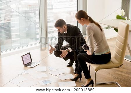 Businessman and businesswoman discussing modern commercial or residential interior design ideas, designers brainstorming, planning new project with digital layout,