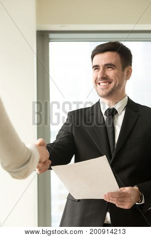 Happy smiling businessman wearing suit shaking female hand, holding document, company director congratulating new hire employee offering employment contract, awarding with diploma, vertical view