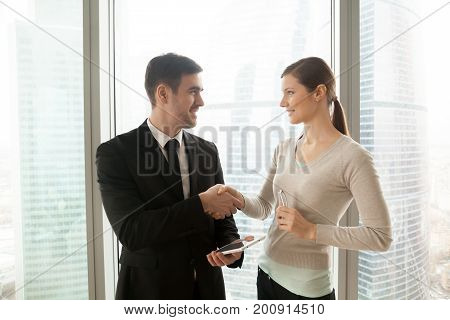 Smiling businessman with tablet shakes businesswoman hand, satisfied executives conclude deal in digital marketing, happy partners agreed to launch own business app, smart contracts, media placement